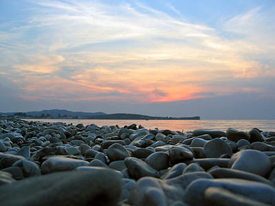 black pebbles near ocean during golden hours