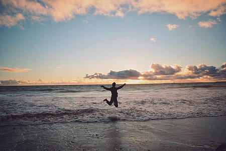 Person Taking Picture in Seashore during Sunset