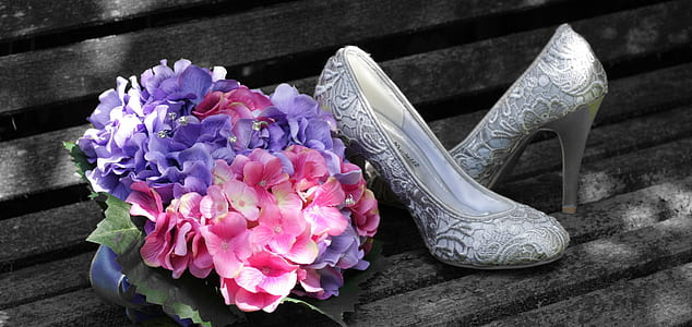 pair of silver shoes and bouquet of flowers
