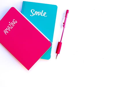 pink and blue books near pink click pen