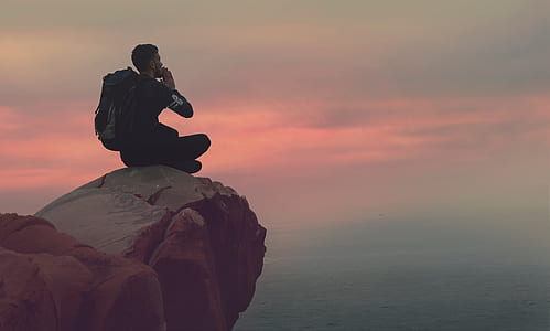 man sitting on mountain ledge at sunset