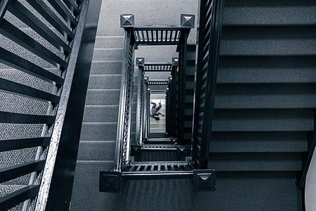 man lying on the floor near stairways