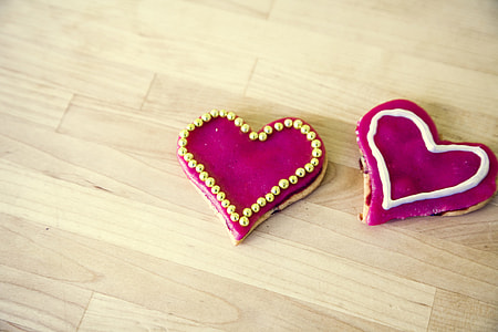two heart-shape pink textiles on brown wooden floor