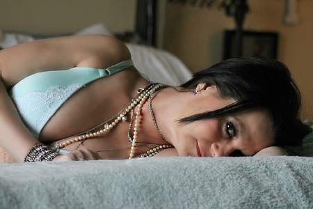 woman lying on bed wearing teal brassiere