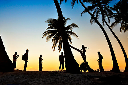 People enjoying the palm-tree beach at sunset in the Maldives