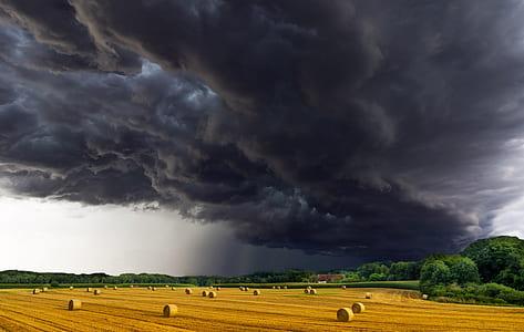 dark clouds under hay rolls