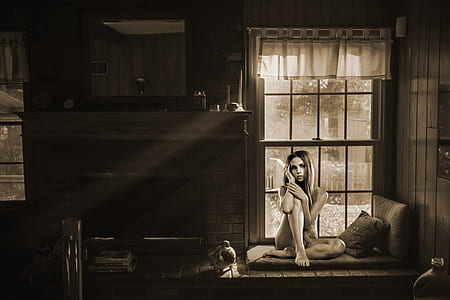 grayscale photo of woman sitting on sofa near window
