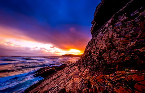 brown rocky mountains beside sea during sunset