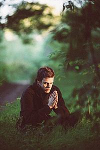 man wearing black jacket praying in forest