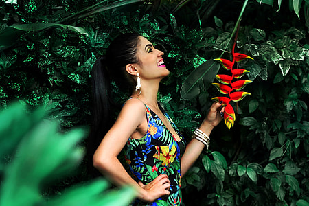 Woman with smile standing by tropical forest plants