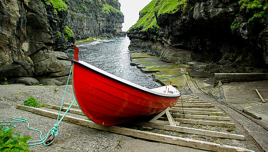 red and white rowboat near body of water surrounded by black mountain