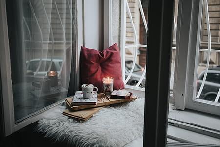 red throw pillow near window