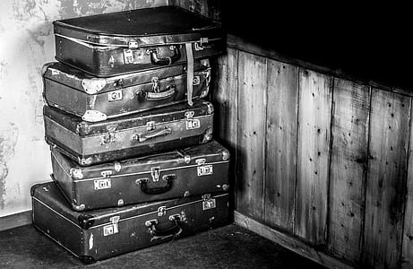 stacked briefcase in grayscale photography
