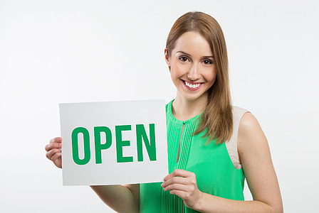 woman holding open-text signage