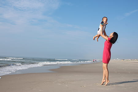 woman raising child near seashore