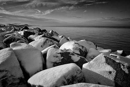 Winter time scene of some snow-covered rocks. Image captured on the coast of Kent, England