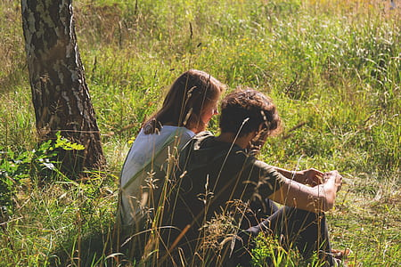 man and woman sitting on grass at daytime
