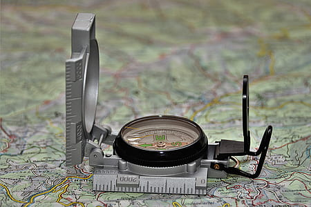 round black and gray analog compass on green map