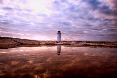 white lighthouse in the desert during daytime