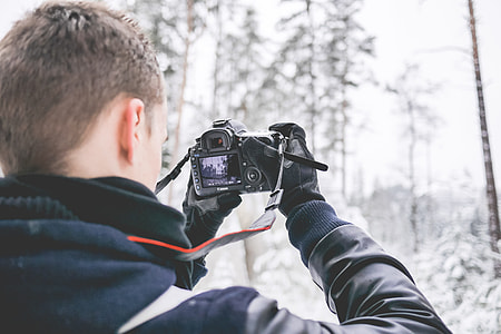 Photographer in Snowy Forest Taking Winter Photos