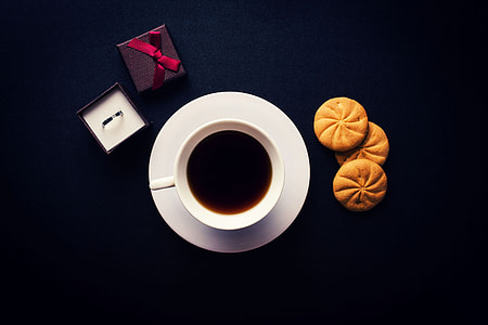 Overhead shot of coffee, biscuits and a ring