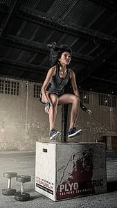woman in grey top jumping over box