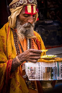 man in yellow and red traditional dress and brown beaded necklace