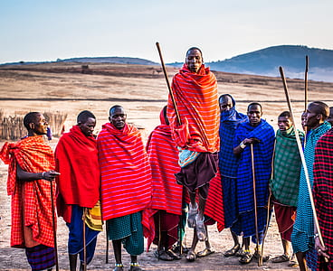 Photo of Group of Men Wearing Assorted Scarves Holding Sticks