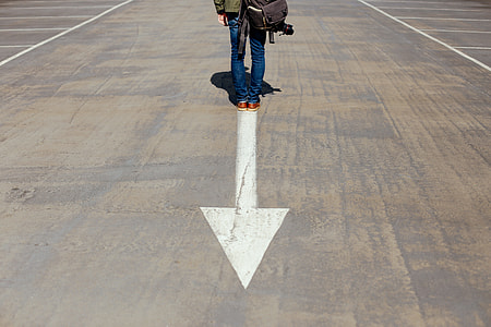 person standing on gray and white concrete pavement with arrow