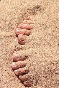 human foot under brown sand
