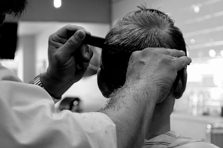 grayscale photography of barber cutting hair