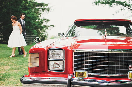 red car in front of bride and groom