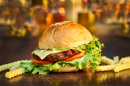 shallow focus photography of hamburger with tomato, lettuce, and cheese beside bunch fried fries