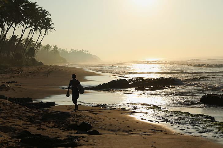 male surfer walking on seashore