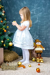 girl in white and light-blue dress holding gold-colored Christmas bauble