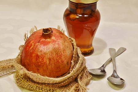 promegranate fruit beside amber glass bottle and two gray teaspoons