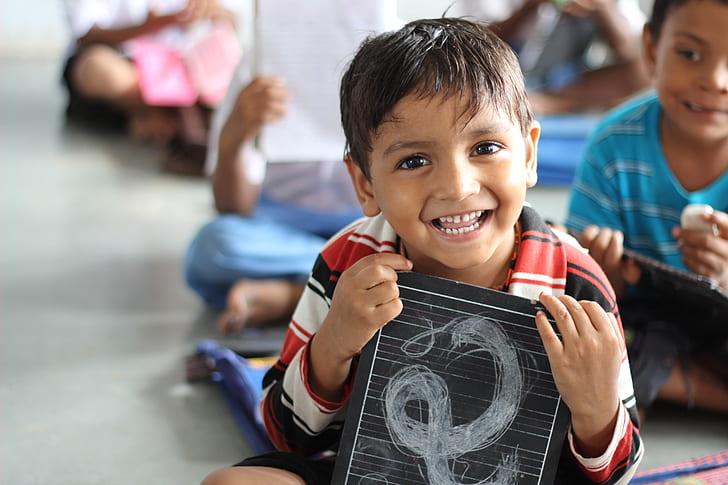 boy holding a black board smiling