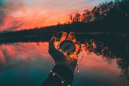 person holding compass and string light near body of water during sunset