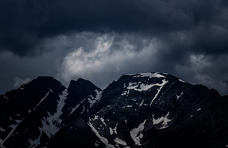 photography of snow coated mountains under nimbus clouds