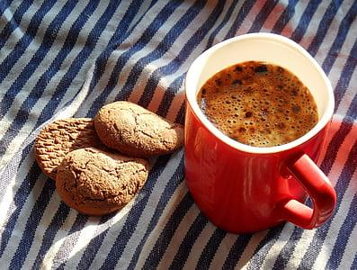 coffee in red and white ceramic mug near three cookies
