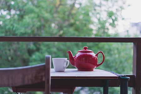 red ceramic teapot near white ceramic mug on brown wooden table