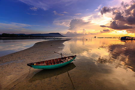 green and brown boat on seashore during golden hour
