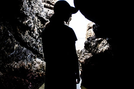 silhouette photography of person inside a cave during daytime