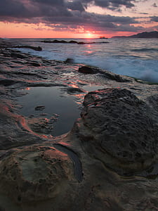 Gray and Black Rock Formation Near the Ocean during Sunset