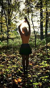 women's black skirt standing inside the forest
