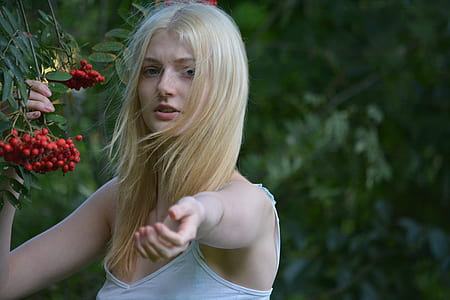 woman wearing white spaghetti strap top reaching out left hand and right hand holding bunch of red berries