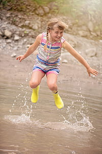 jumping brown haired girl on body of water