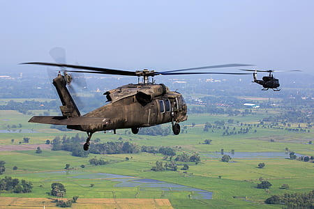Brown Helicopter Flying Above Green Field during Daytime