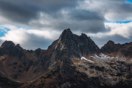 mountain summits under gray cloudy sky