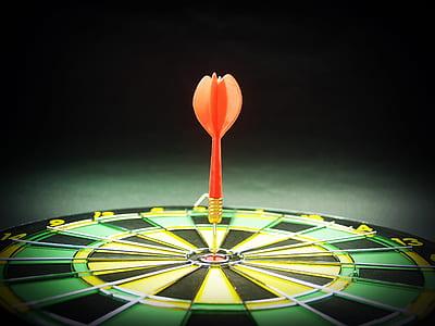 orange arrow on dartboard closeup photo
